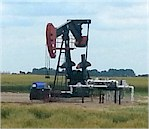 Pumpjack in wheat field
